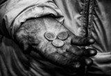 Dirty hands of a beggar whith some coins