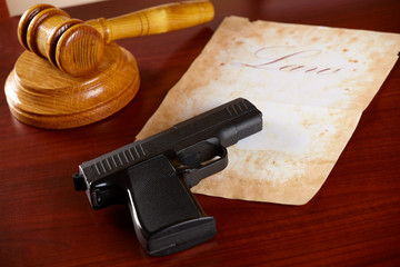 Judges gavel with gun and very old paper