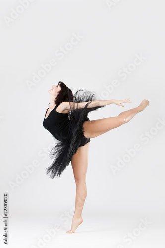 Beautiful ballerina doing split against white background