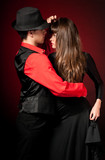 Young couple passion dancing on red light background.