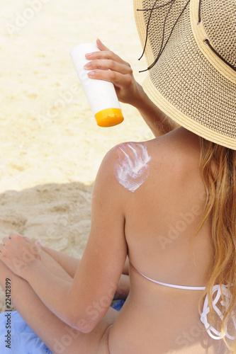 woman applying sunscreen lotion at the beach © mangostock