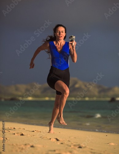 female triathlete running at the beach at sunrise in hawaii