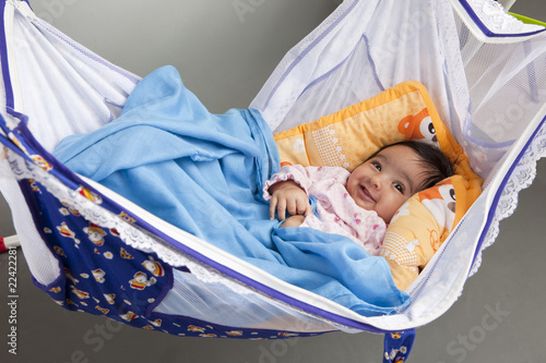 Smiling Baby in a traditional, hammock-style cradle