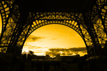 Orange sunset under Eiffel Tower arches
