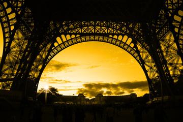Orange sunset under Eiffel Tower arches