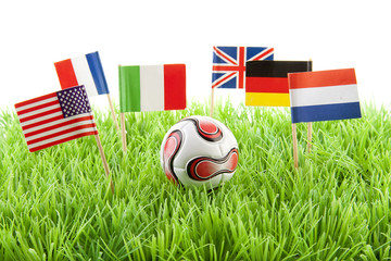 Flags and ball on soccer field over white background