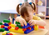 Fototapety Little girl play with building bricks in preschool