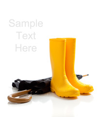 Yellow rainboots and black umbrella on white