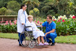 doctor pushing patient in wheelchair in park