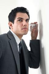 junger business mann hört an einer wand mit glas