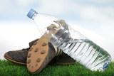 Black soccer shoes and water bottle on grass