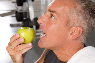 A side view of a mature sportsman eating an apple