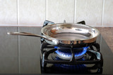 Cooking in a frying pan on a gas stove poster