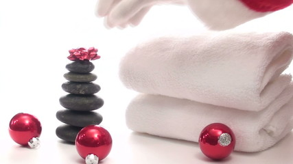 Santa places bow on Spa massage stones - HD