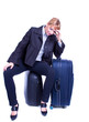 businesswoman sits on black suitcase and waiting for somebody