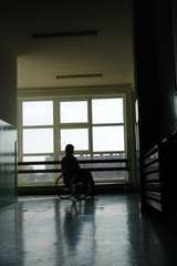 Silhouette of wheelchair woman looking through window