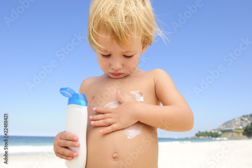 cute child applying  sunscreen  at the beach