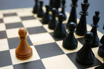 Wood chess game shows white brave pawn facing stronger enemy.