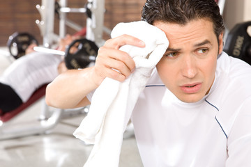 Exhausted man cleaning sweat from his face