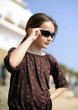 Young girl adjusting sunglasses