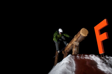 snowboarder on tree rail at night