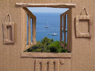 casa di cartone al mare con barche