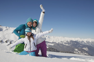 Couple and daughter in ski wear, playing in snow
