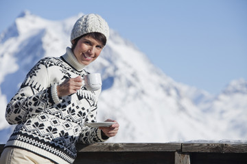 Young woman drinking coffee, mountains in background