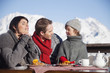 Couple and daughter eating on balcony at ski resort
