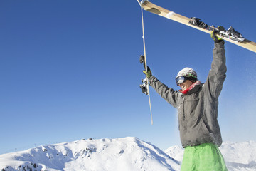 Young man holding his skis above his head