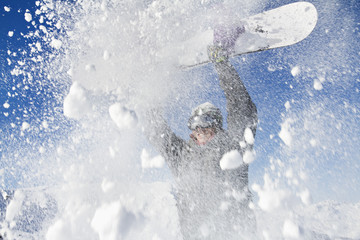Young man holding his snowboard above his head