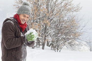Young man making a snowball