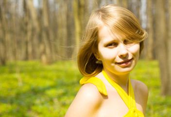 Girl smiling in sunny spring field. Copy space