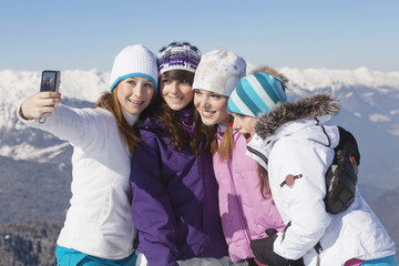 Four teenage girls in ski clothes, taking self portrait