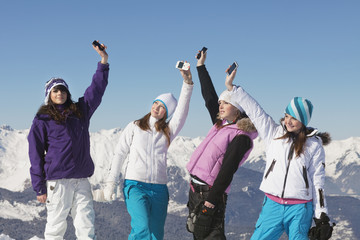 Four teenage girls in ski clothes, with their mobile phones in air