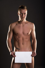 Muscular naked man holding a space box
