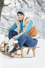 Young woman sitting on sled