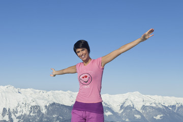 Young woman with arms raised, smiling at camera, mountains in background