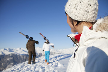 Woman looking at father and daughter carrying skis