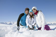 Couple and daughter sitting in snow, smiling at camera
