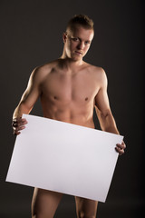 Young naked male stands straight holding a space box