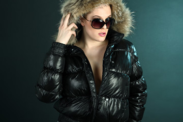 Tough girl in black jacket and sunglasses on cyan background