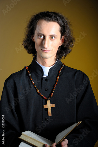 conceptual portrait of Praying priest with wooden cross
