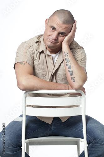 Homme tatou assis sur une chaise photo libre de droits for Assis sur une chaise