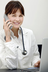 young caucasian woman doctor on the phone with laptop