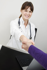 young caucasian woman doctor and patient shake hands