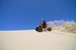 Large sand spray from ATV quadbike rider in the dunes