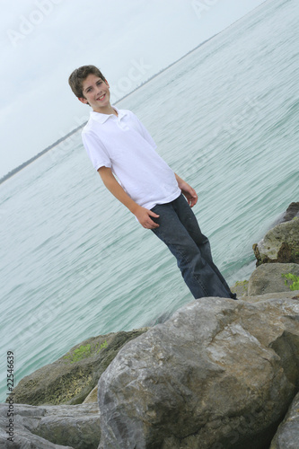 boy standing on rocks at the beach