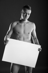 Young naked man holding a space box