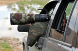 Bird photographer taking photos with camouflaged telephoto lens.